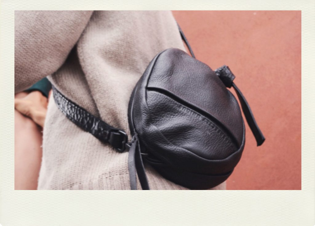 Man with a small leather bag wearibg a wool jumper