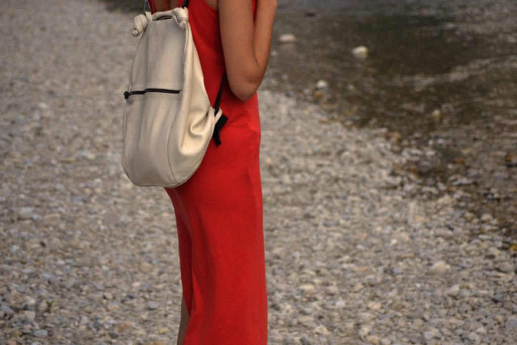 girl in red dress with white backpack
