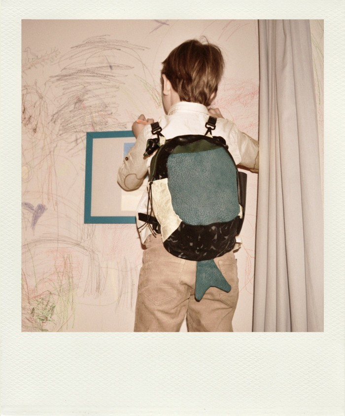 A boy with a backpack drawing on a wall