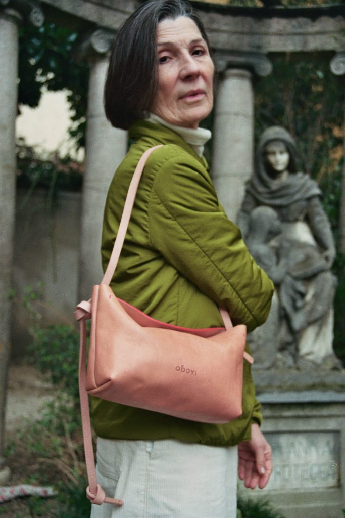 Woman in green jacket carying pink leather bag