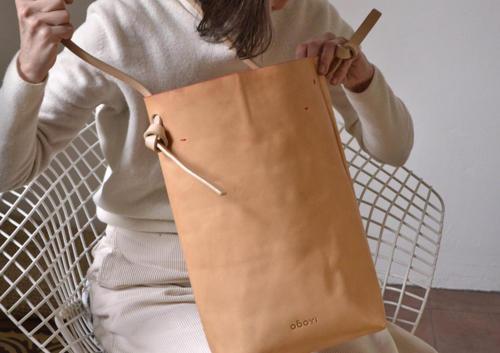 Woman holding beige shopper bag in leather
