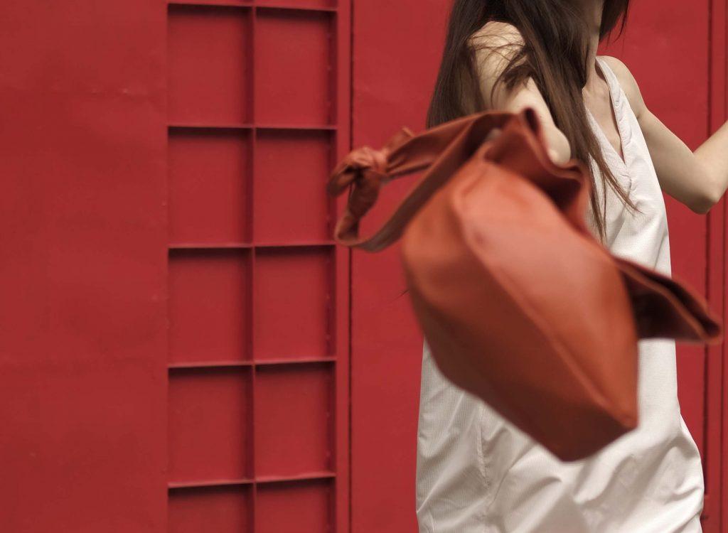 Woman in white holding lightweight orange bag