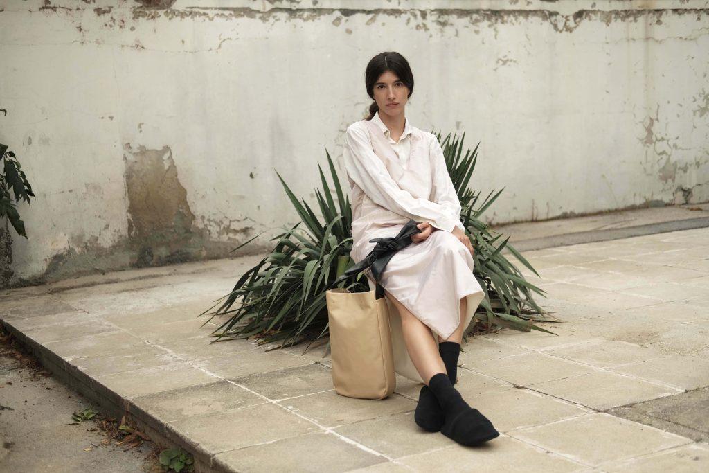 Woman in a silk long reversible dress with a beige lightweight leather shopper