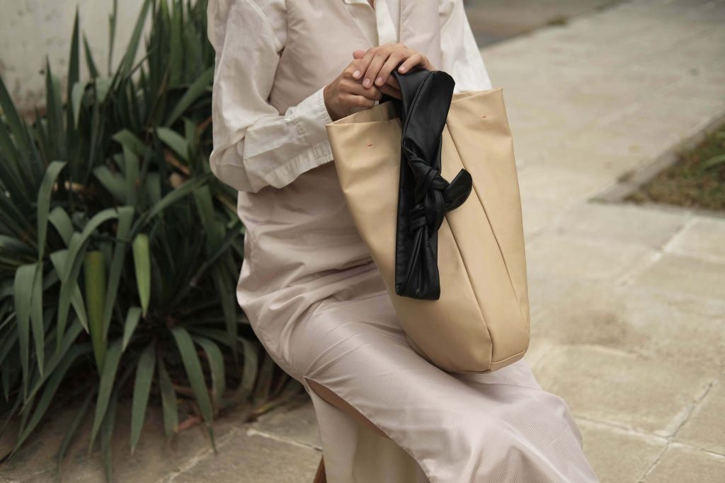 Woman in white reversible dress and shirt holding beige lightweight shopper bag