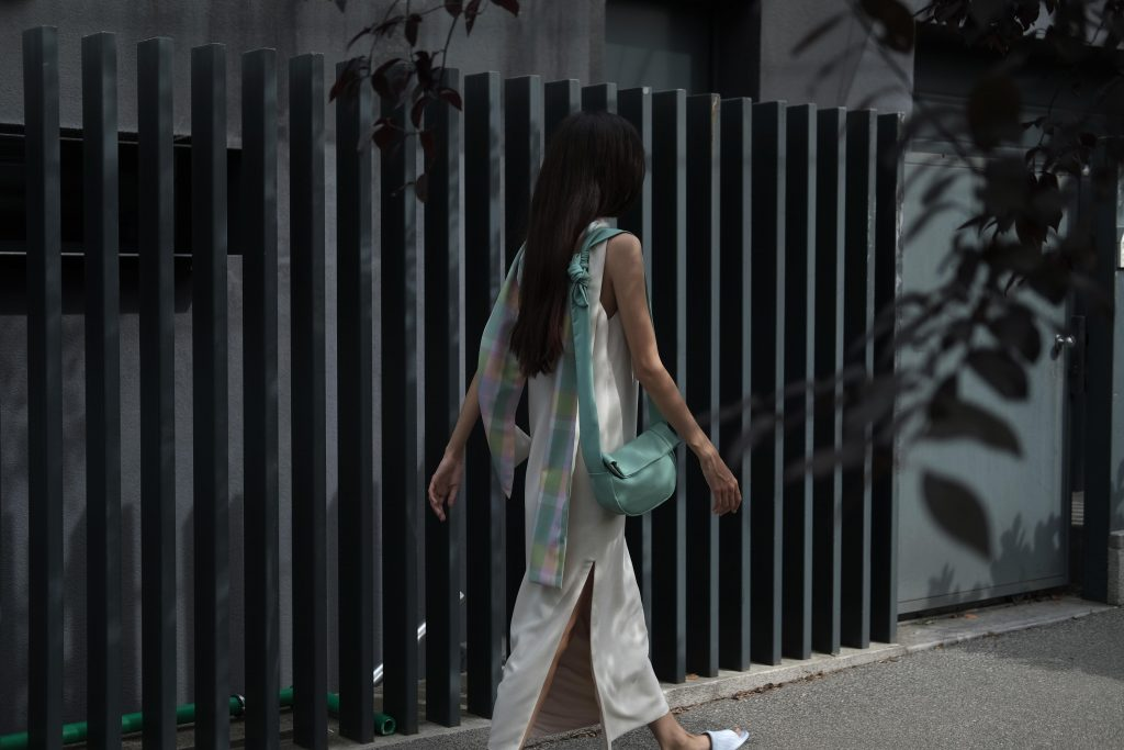 Woman in white with mint leather bag