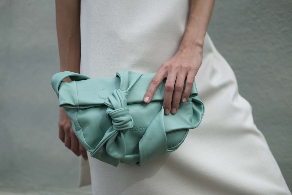 Woman in white holding mint small leather bag